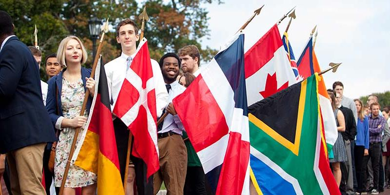 Bryn Athyn College Students processing on Charter Day holding international flags
