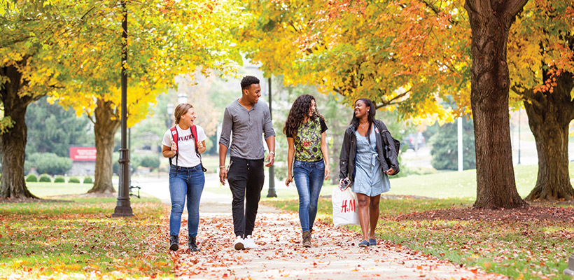 Bryn Athyn College students walking to class under the fall leaves