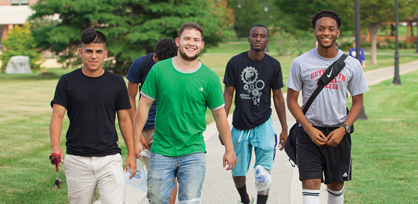 four male students walking near the residence halls