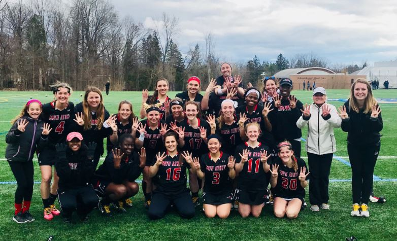 women's lacrosse team posing together with big smiles and holding up eight fingers, signifying their winning streak