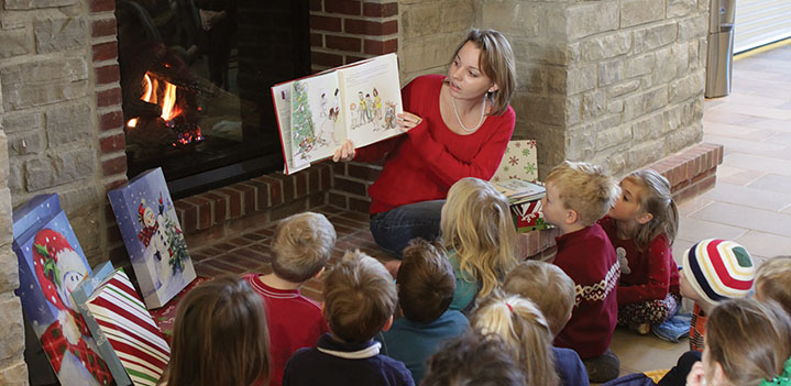 Education reads to early education class by a cozy fire in the Brickman Center at Bryn Athyn College