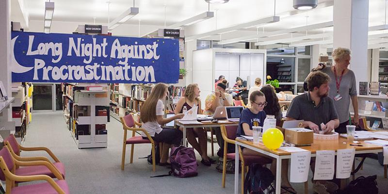 Bryn Athyn College students and support teachers in the library in front of a large blue banner for the long night against procrastination event.
