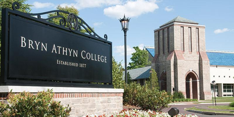 The Bryn Athyn College sign stands in the foreground with the Brickman Center and Swedenborg Library behind it at Bryn Athyn College