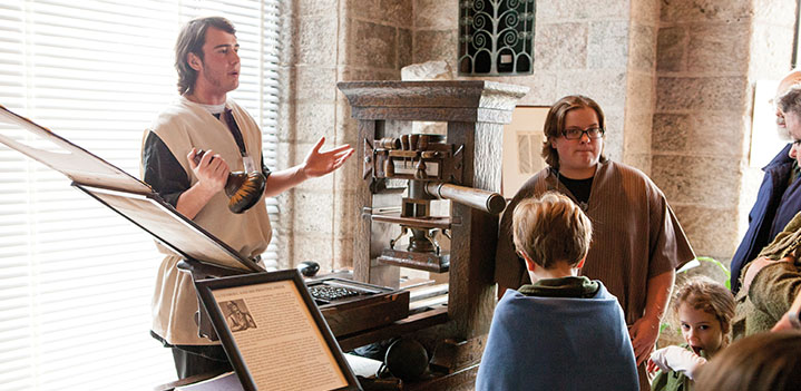 Student demonstrates a printing press to Glencairn visitors