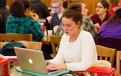 Bryn Athyn College student writing on a laptop