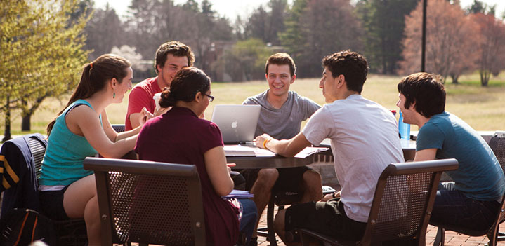 Students working on a group project at a patio table outdoors
