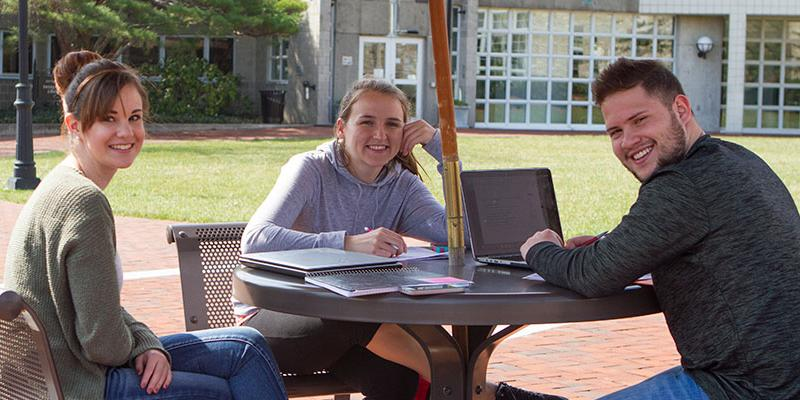 Students working on a project on the Brickman patio at Bryn Athyn College